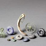 Perles et pendentifs en verre, bronze, pierre, canine de porc. Diam. de la rouelle: 4,8cm. Cliché Y. André, MCAH.