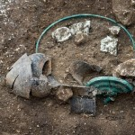 Le dépôt funéraire comprend plusieurs éléments de vaisselle, ici une élégante bouteille en céramique, un bassin en bronze et un couvercle.