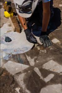 Nettoyage du sol en opus sectile  de la maison de Thalie et Pan (IIe-IIIe s.). Photo Flore Giraut. © Archeodunum.
