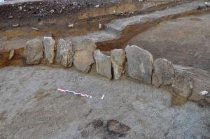 Ces grandes dalles, récupérées de la nécropole du néolithique, ont servi de marqueurs aux structures plus tardives, notamment cet important tumulus du bronze final. Photo Archeodunum SA.